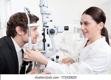 Eye Woman Doctor Adjusting Slit Lamp / handsome man during a cornea exam / the oculist in eyes clinic doing crystalline lens diagnostic / high technology concept eyes care
