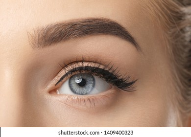 Eye of young woman with beautiful eyebrow after correction, closeup