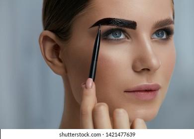 Eyebrow coloring. Woman applying brow tint with makeup brush closeup. Girl model using liquid peel-off brow gel, beauty product on eyebrows