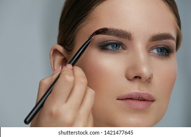 Eyebrow coloring. Woman applying brow tint with makeup brush closeup. Girl model using liquid peel-off brow gel, beauty product on eyebrows