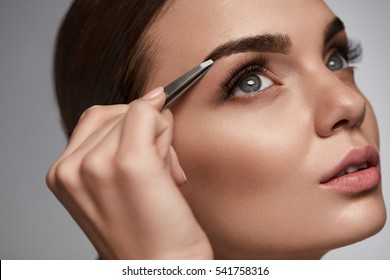 Eyebrow Correction. Closeup Of Beautiful Young Woman With Perfect Makeup And Long Lashes Plucking Eyebrows. Portrait Of Sexy Female Model Face And Tweezers Near Brows. Beauty Concept. High Resolution
