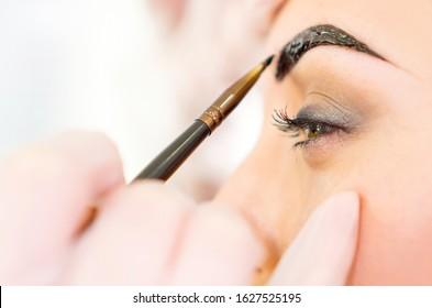 Eyebrow correction, eyebrows tinting treatment close-up.
