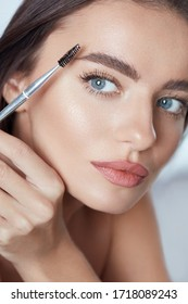 Eyebrow Makeup. Woman Brushing Brows With Brush. Beautiful Girl With Blue Eyes And Perfect Skin Close Up Portrait.