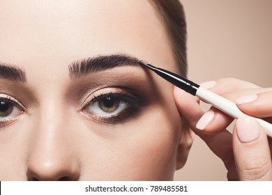 Eyebrow shadow applying, brow modelling makeup, eye closeup. Female model face with fashion make-up, beauty concept
