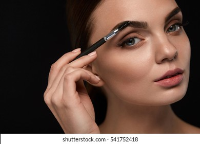 Eyebrows Brushing. Closeup Of Beautiful Young Female Model Face With Professional Makeup And Brow Brush On Black Background. Sexy Woman Brushes Perfect Brows. Beauty Cosmetics. High Resolution Image