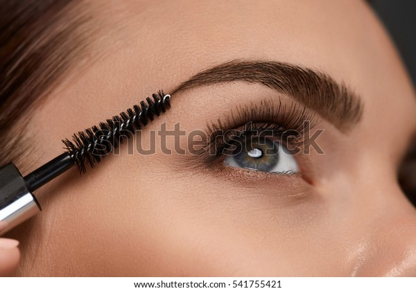Eyebrows Care. Closeup Of Woman Beautiful Blue Eye, Perfect Shaped Brow, Long Eyelashes With Professional Makeup And Brow Gel Brush. Young Female Model Shaping Brown Eyebrows. High Resolution Image