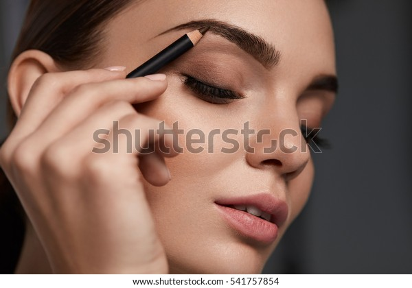 眉毛メイク。目を閉じた美しい女性、茶色の眉毛を描いた完璧な化粧。グレイの黒い背景にスムーズな肌を持つ女性モデルの美顔の接写。高解像度