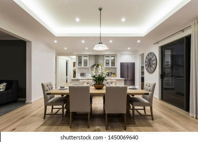 Ein Blick auf den modernen Speisesaal, der an eine modulare Küche mit einem Esstisch mit 6 Sitzplätzen und einem hellen, über ihm aufgehängten Licht angeschlossen ist.