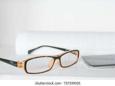 Eyeglass on book