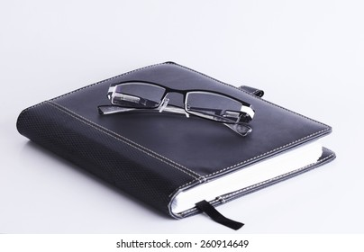 Eyeglass on Business memory Book Isolated on white background