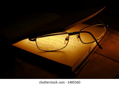 eyeglasses between illuminated pages of an old book
