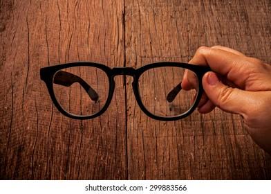 Eyeglasses, Clear Glasses, Black Frame Fashion Vintage Style, Hand Holding  on Wood Desk Background, Rustic Still Life Style.