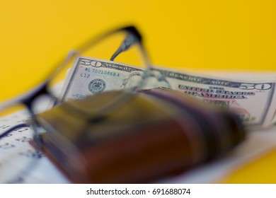 Eyeglasses and full wallet with dollars banknotes on a calendar sheet blurred