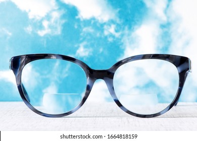 Eyeglasses Glasses with Bifocals and Black Blue Frame smudged agaist a blue and cloudy sky