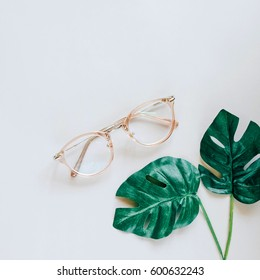 Eyeglasses and green palm leaves on grey background, minimal style with spring and fashion accessory concept
