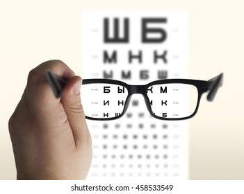 Eyeglasses in hand for eyesight Russian/Cyrillic test chart background, isolated