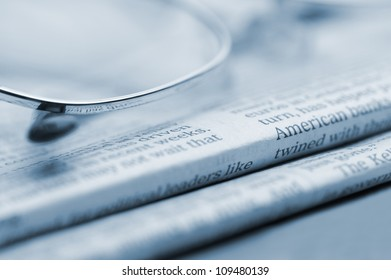 Eyeglasses lie on a pile of newspapers.Blue toned. A photo close up. Selective focus