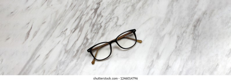 Eyeglasses on black and white marble table texture background, copy space and banner style for text