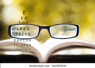 eyeglasses on book with eye vision test chart background