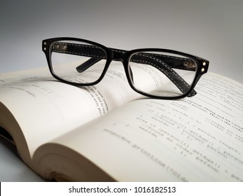 eyeglasses on book on white background with copy space selective focus
