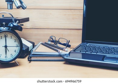 Eyeglasses on books with laptop and alarm clock on wooden table.