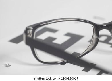 Eyeglasses on eyesight test chart background close-up.
