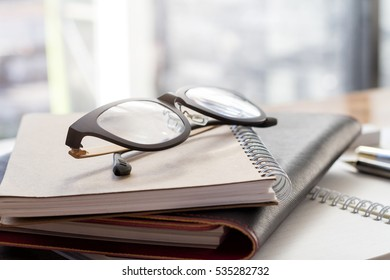 eyeglasses on notebook on window background