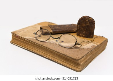 Eyeglasses and paper case on old book, isolated