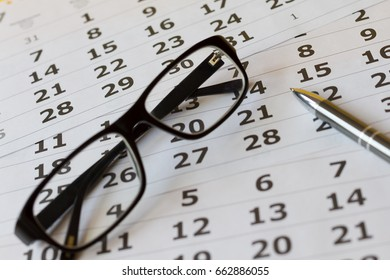 Eyeglasses with pen on a calendar sheets