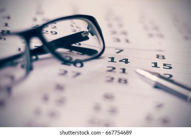 Eyeglasses with pen on a calendar sheets blurred