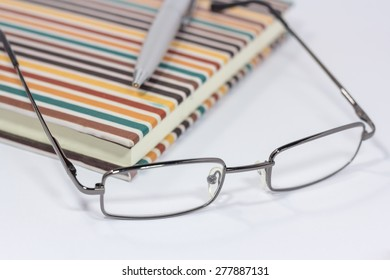 eyeglasses and pen on notebook