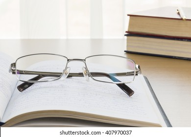 Eyeglasses put on notebook on wood table with natural light from window