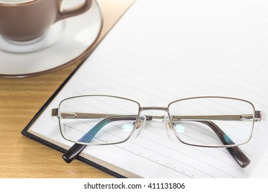 Eyeglasses put on notepad open blank page on wood table