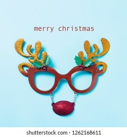 eyeglasses in the shape of a reindeer face and the text merry christmas on a blue background