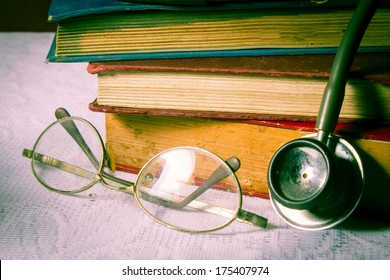 Eyeglasses and stethoscope with books.