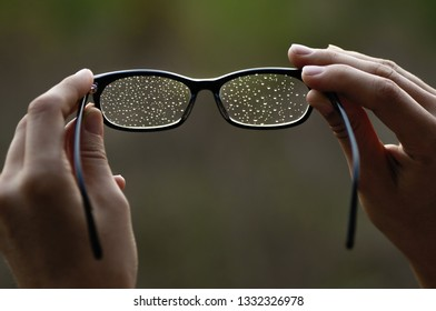Eyeglasses with water drops in the woman hands.