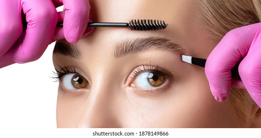 Eyelash artist plucks eyebrows with tweezers. Beautiful woman having Permanent Make-up Tattoo on her Eyebrows. Professional makeup and cosmetology skin care.