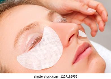 Eyelash care treatment procedures. Woman doing eyelashes lamination, staining, curling, laminating and extension for lashes.