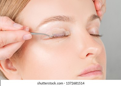 Eyelash care treatment procedures. Woman doing eyelashes lamination, staining, curling, laminating and extension for lashes.