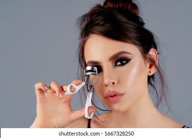 Eyelash curler. Beautiful girl using eyelash curler on long eyelashes. Curly eye lashes. Portrait of beautiful young woman using beauty tool on curly long eyelashes