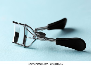 Eyelash curler with black handles on a blue background, close up