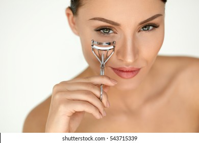 Eyelash Curler. Portrait Of Beautiful Young Woman Using Beauty Tool On Curly Long Eyelashes. Closeup Of Female Model Face With Smooth Skin, Perfect Natural Makeup. High Resolution