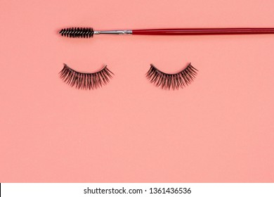 Eyelash extension, concept. Women's eyelashes and brush for styling and combing eyebrows on a pink background, glamour and makeup
