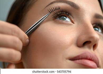 Eyelash Extension. Hand With Tweezers Applying Artificial Eyelashes On Beautiful Woman Eyes. Closeup Of Female Model Face With Long Fake Eye Lashes. Extremely Long Lashes. High Resolution Image