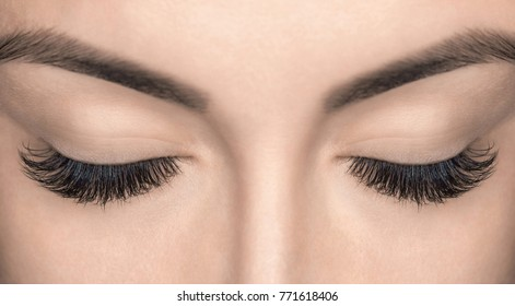Eyelash extension procedure. Beautiful Woman with long lashes in a beauty salon.