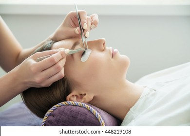 Eyelash Extension Procedure.  Beauty Model with  Perfect Fresh Skin and Long Eyelashes. Slincare, Spa and Wellness. Make up,  Hair and Lashes. Close up.