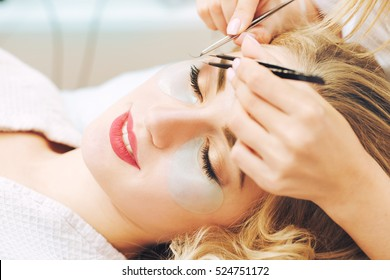 Eyelash extension procedure in beauty salon.