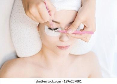 Eyelash Extension Procedure. Close up view of beautiful Woman with Long Eyelashes. Stylist holding tweezers, tongs and making lengthening lashes for girl in a beauty salon. Beauty Concept.