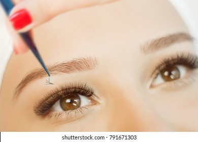 Eyelash Extension Procedure. Close up view of beautiful brown Woman Eye with Long Eyelashes. Stylist holding tweezers, tongs and making lengthening lashes for girl in a beauty salon.