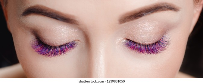 Eyelash extension procedure. Large eyes closed beautiful girls with color lash pink.
